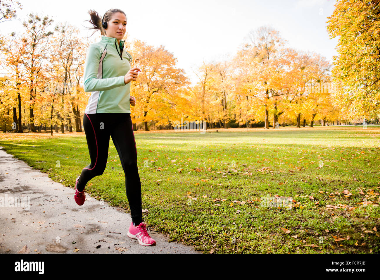 Young woman with headphones running in autumn nature and listening music - Stock Image