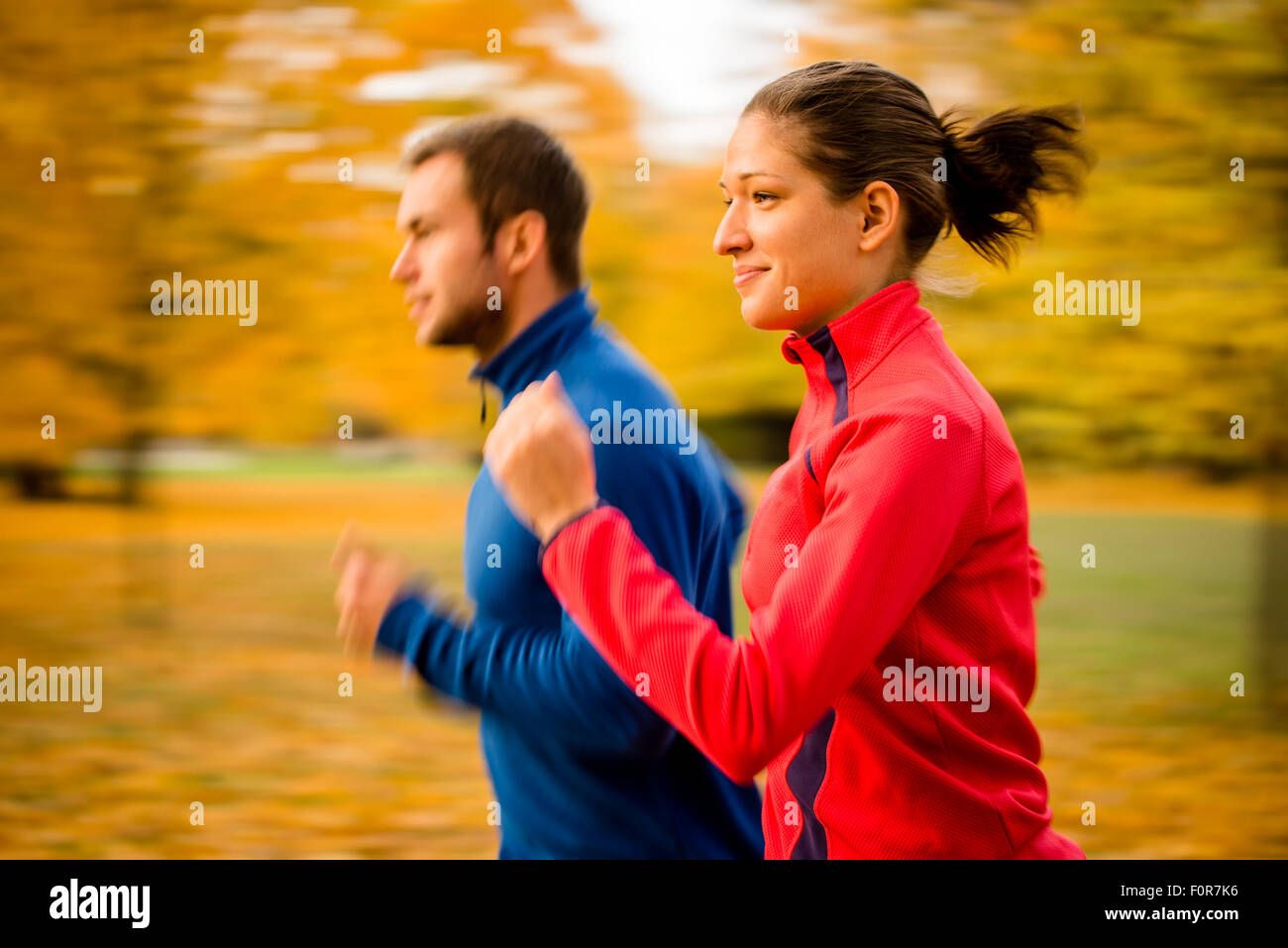 Panning photo of young couple jogging together in nature - Stock Image