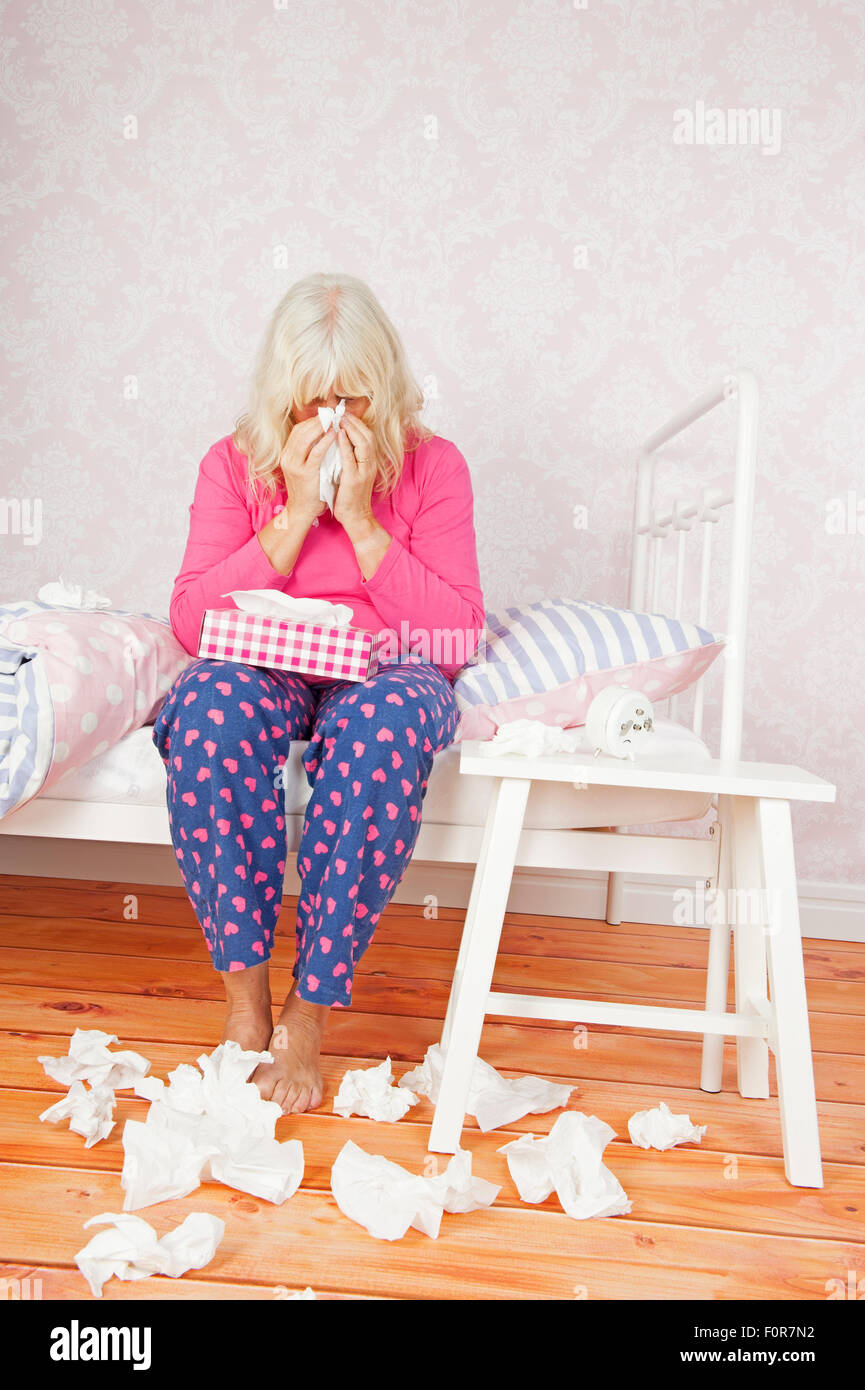 Sad female with pink pajama and tissues blowing her nose while sitting on bed - Stock Image