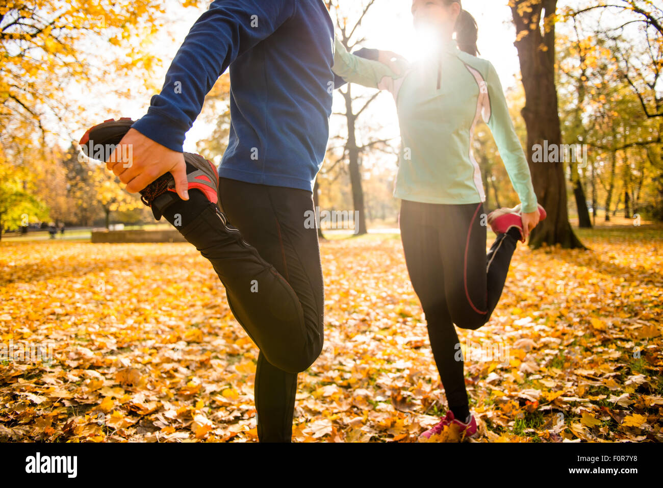 Detail of man and woman stretching legs before jogging in autumn nature - Stock Image