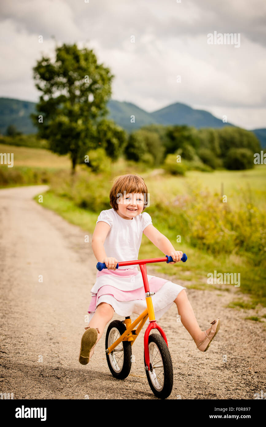 Little child driving her firs bicycle on rural road outdor in nature - Stock Image