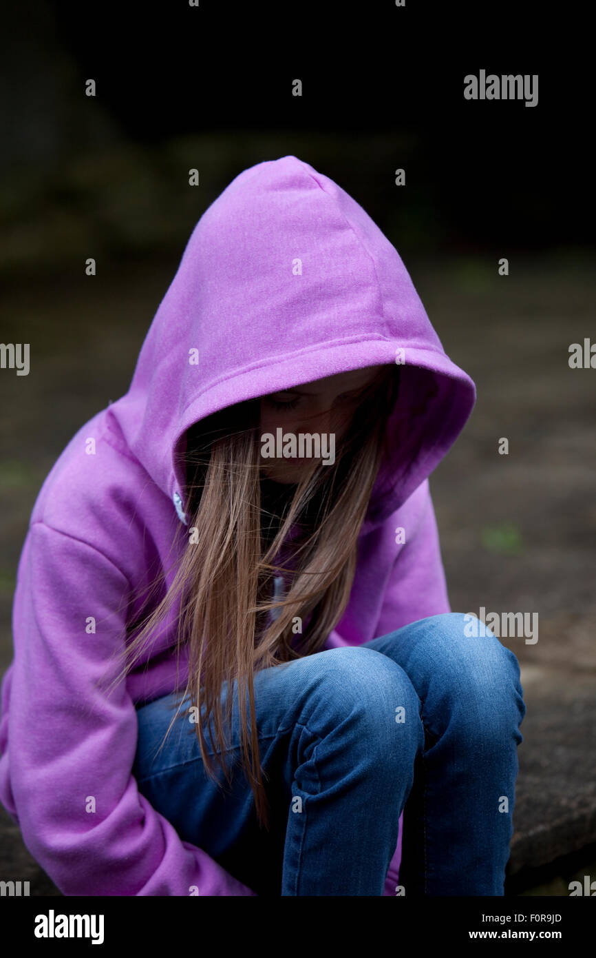 Sad girl in hooded top, sitting with head low in despair - Stock Image