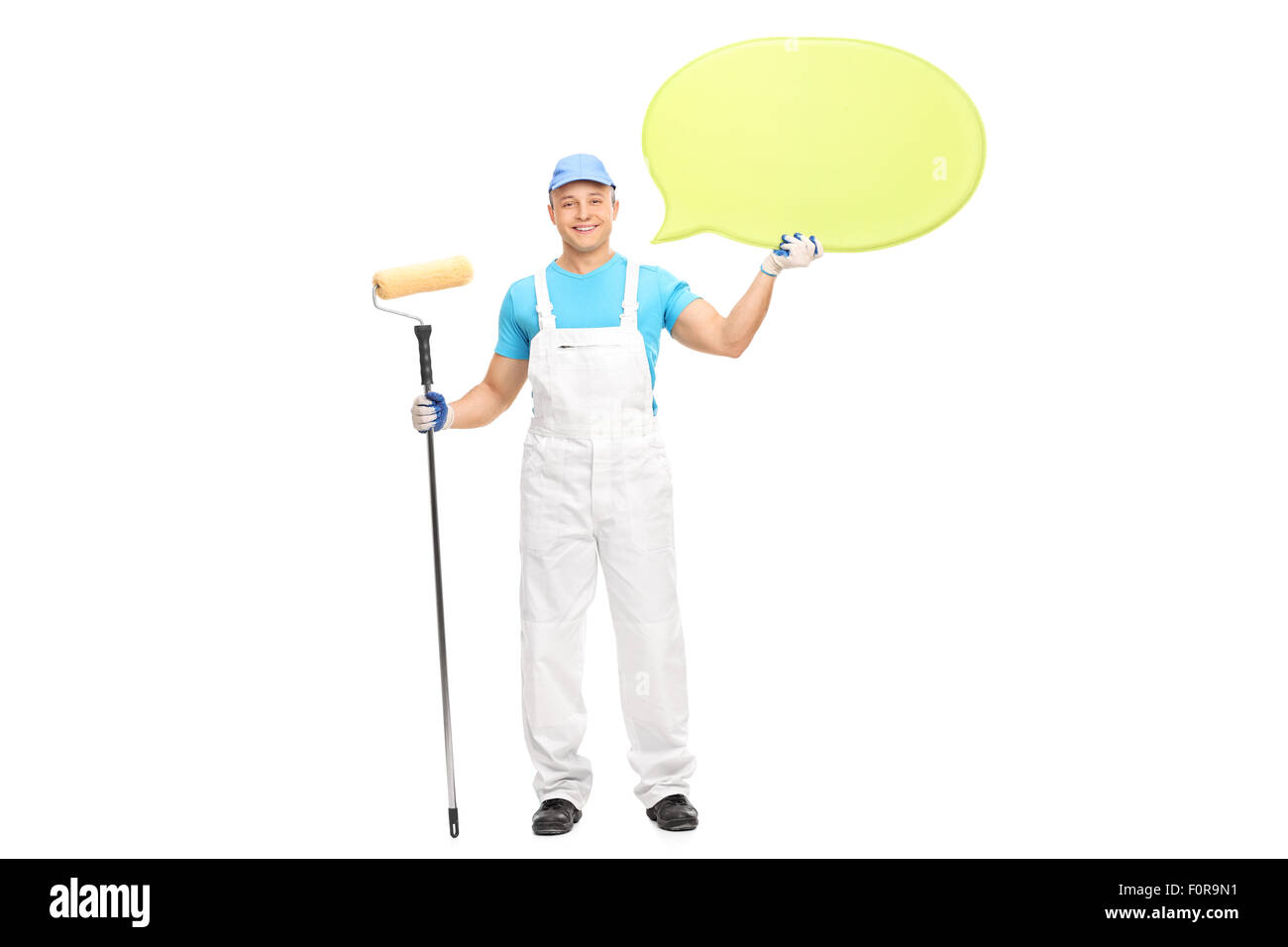 Young male house painter in a white jumpsuit holding a paint roller and a big yellow speech bubble isolated on white - Stock Image