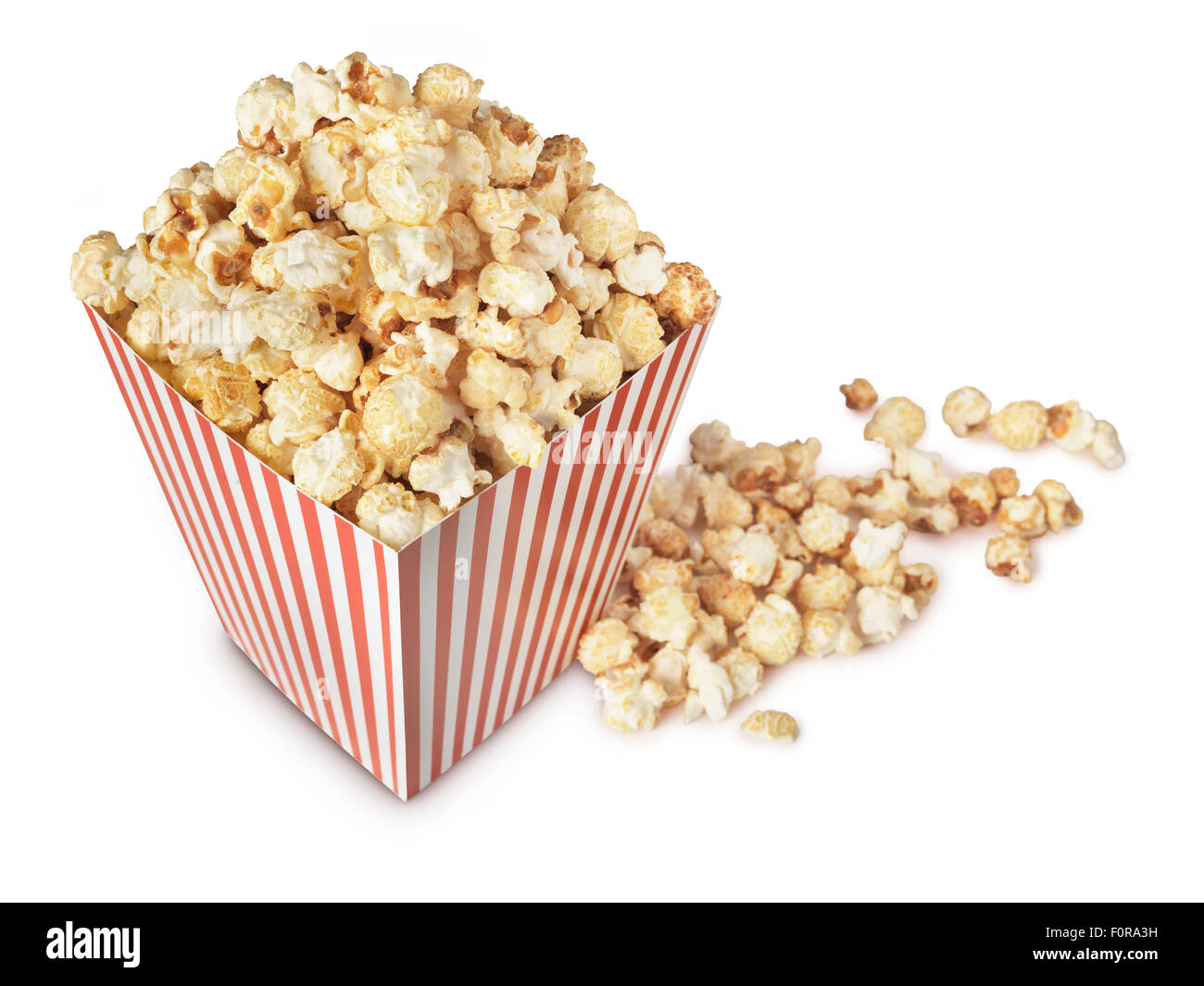 A movie theater popcorn box heaped with the fresh popped, crispy, salty, buttered snack. - Stock Image