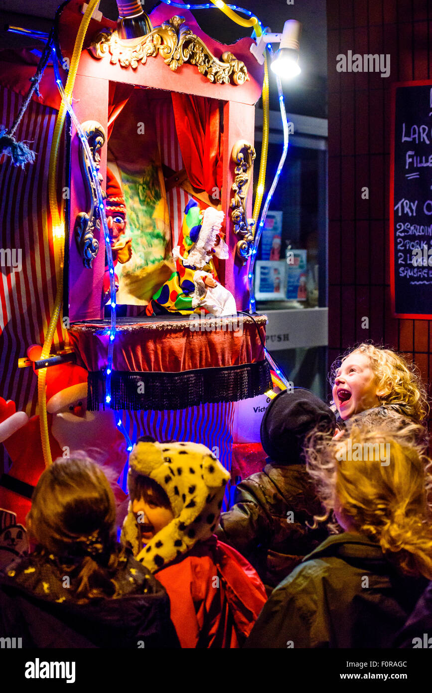 Children enjoy Punch and Judy show during the Victorian Christmas Festival in Garstang Lancashire - Stock Image