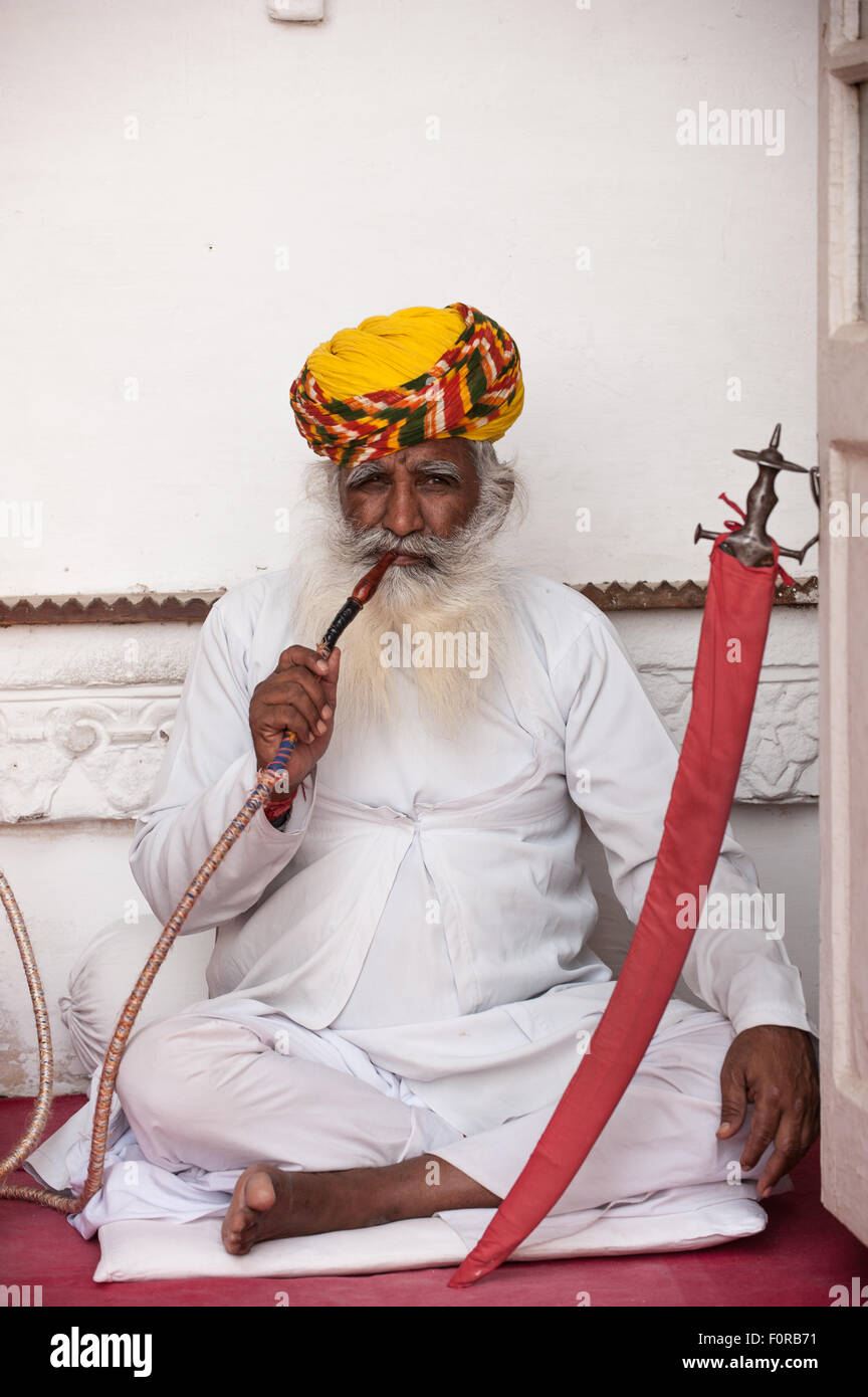Jodhpur, India. Mehrangarh sandstone hill fort of the Marwar rulers. A man in traditional clothes smoking a hookah - Stock Image