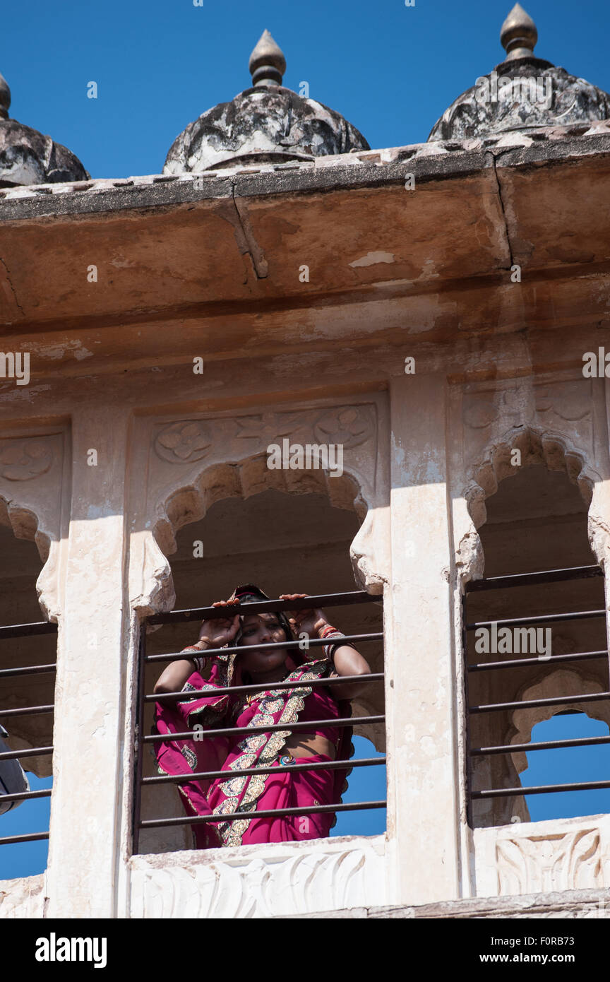 Jodhpur, India. Mehrangarh sandstone hill fort of the Marwar rulers. A woman in Rajasthan pink sari looking through - Stock Image