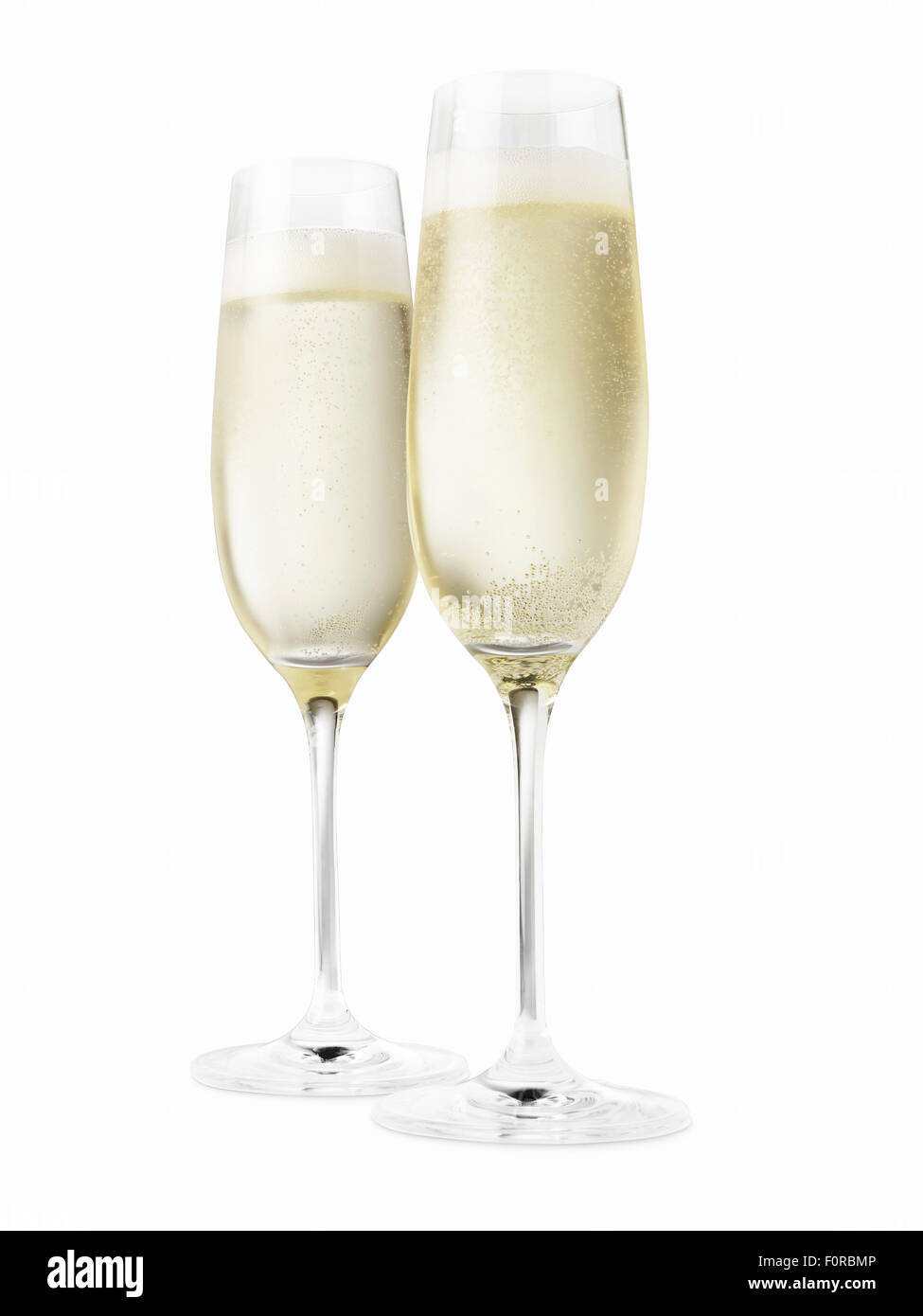 Studio shot of two champagne glasses isolated on a white background. Please note the chilled nature of the liquid - Stock Image