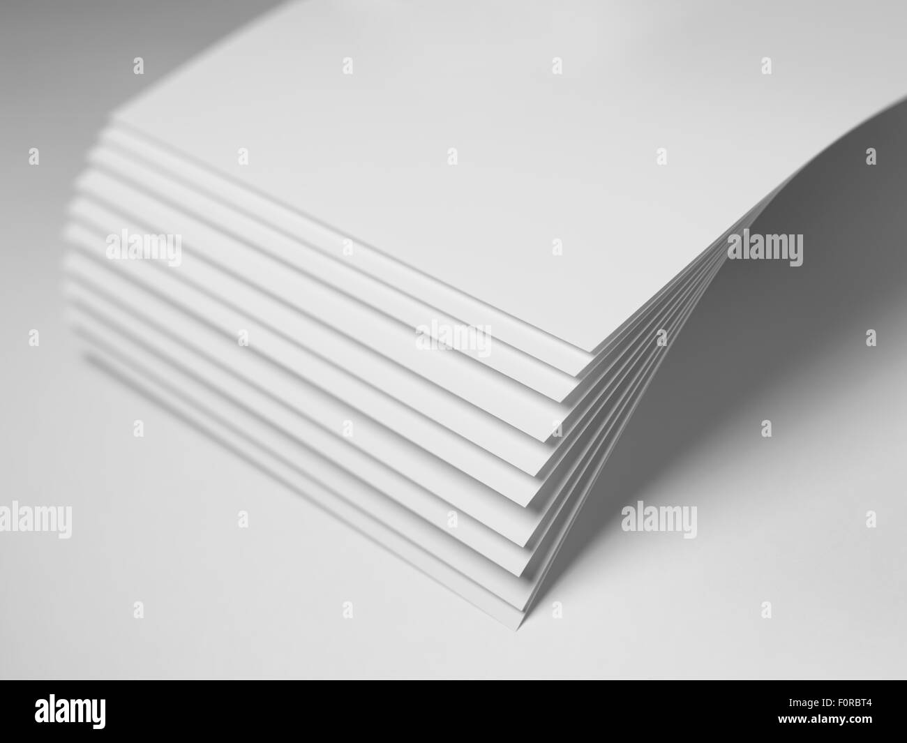 Close up shot of plain white paper with shallow depth of field and focus on the corners and fanned out area. Copy - Stock Image