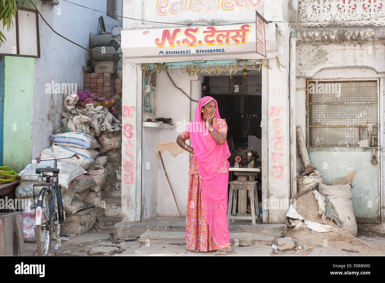 Rajasthan, India. Between Jodhpur and Jaipur. Woman standing outside her tiny sewing shop with her sewing machine - Stock Image