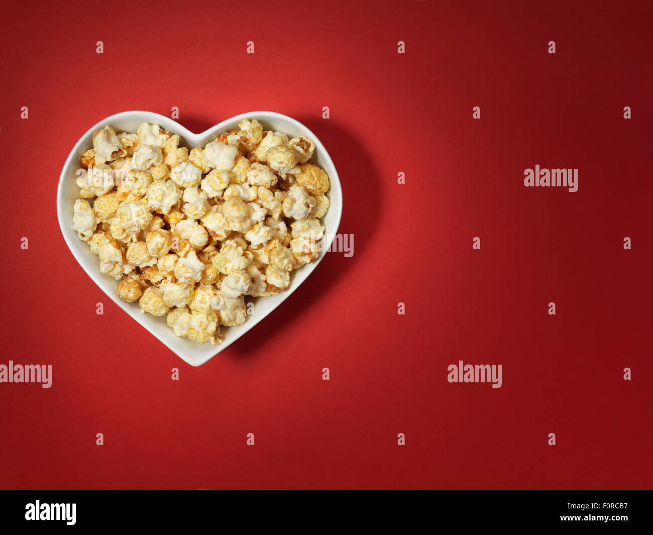 shot of cinema style popcorn in a heart shaped bowl on a bright red background with spotlit, vignette style lighting and offset Stock Photo