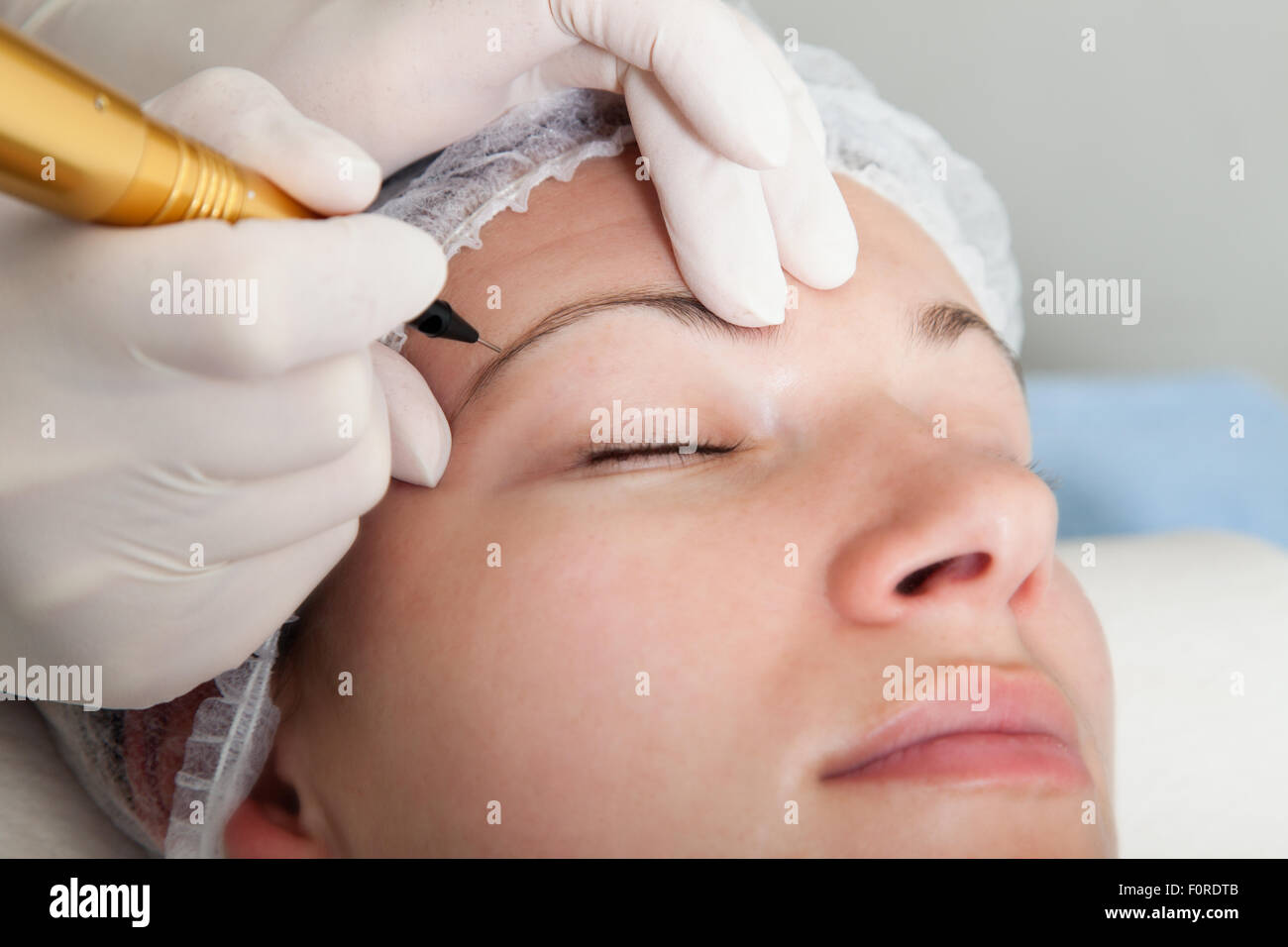 Cosmetologist making permanent makeup - Stock Image