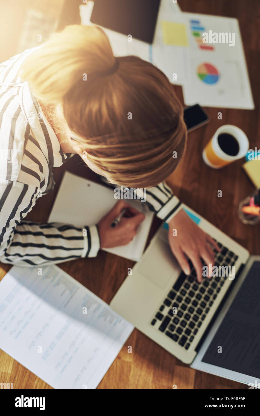 Hardworking successful female entrepreneur working at her desk in her home office writing notes as she researches - Stock Image