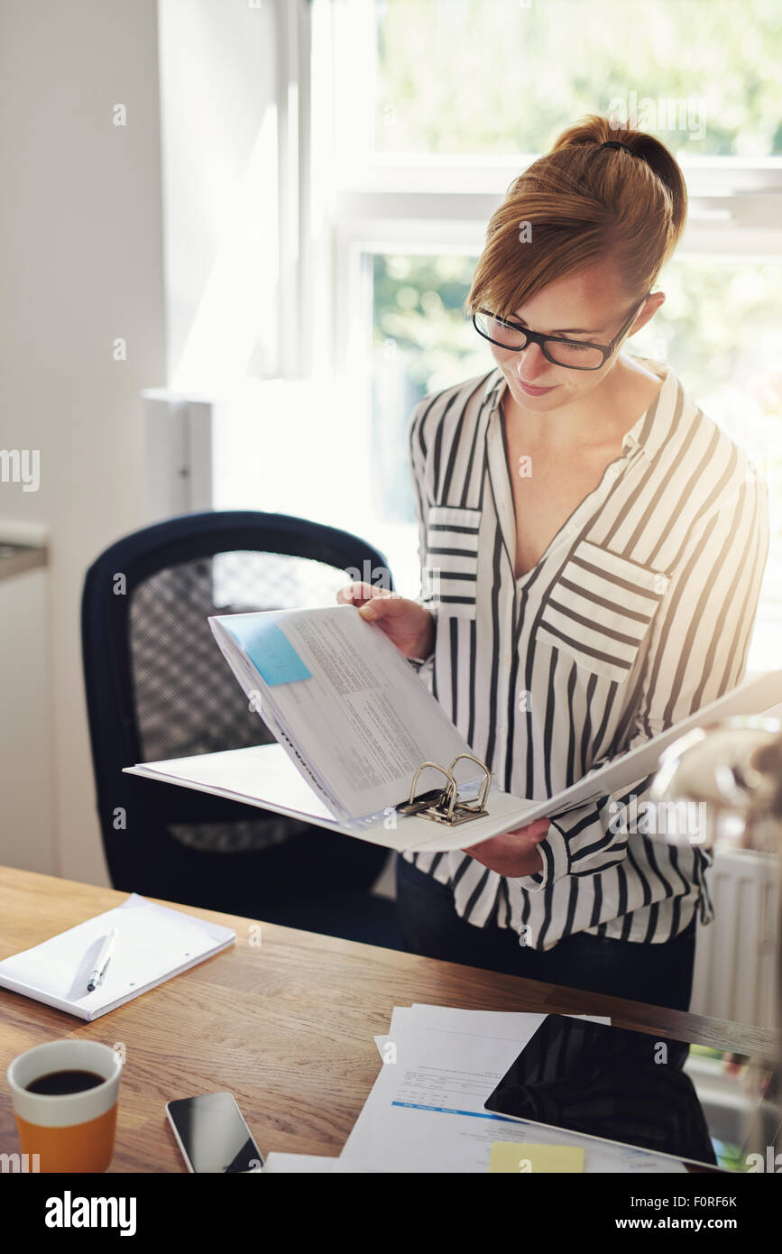 Young businesswoman working at home standing in her office reading notes in a binder with a serious expression - Stock Image
