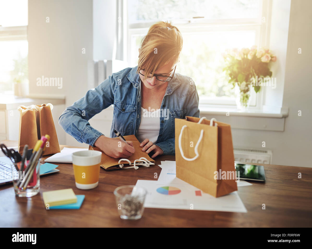 Young businesswoman designing packaging for her new start-up online business sitting at her desk at home working - Stock Image