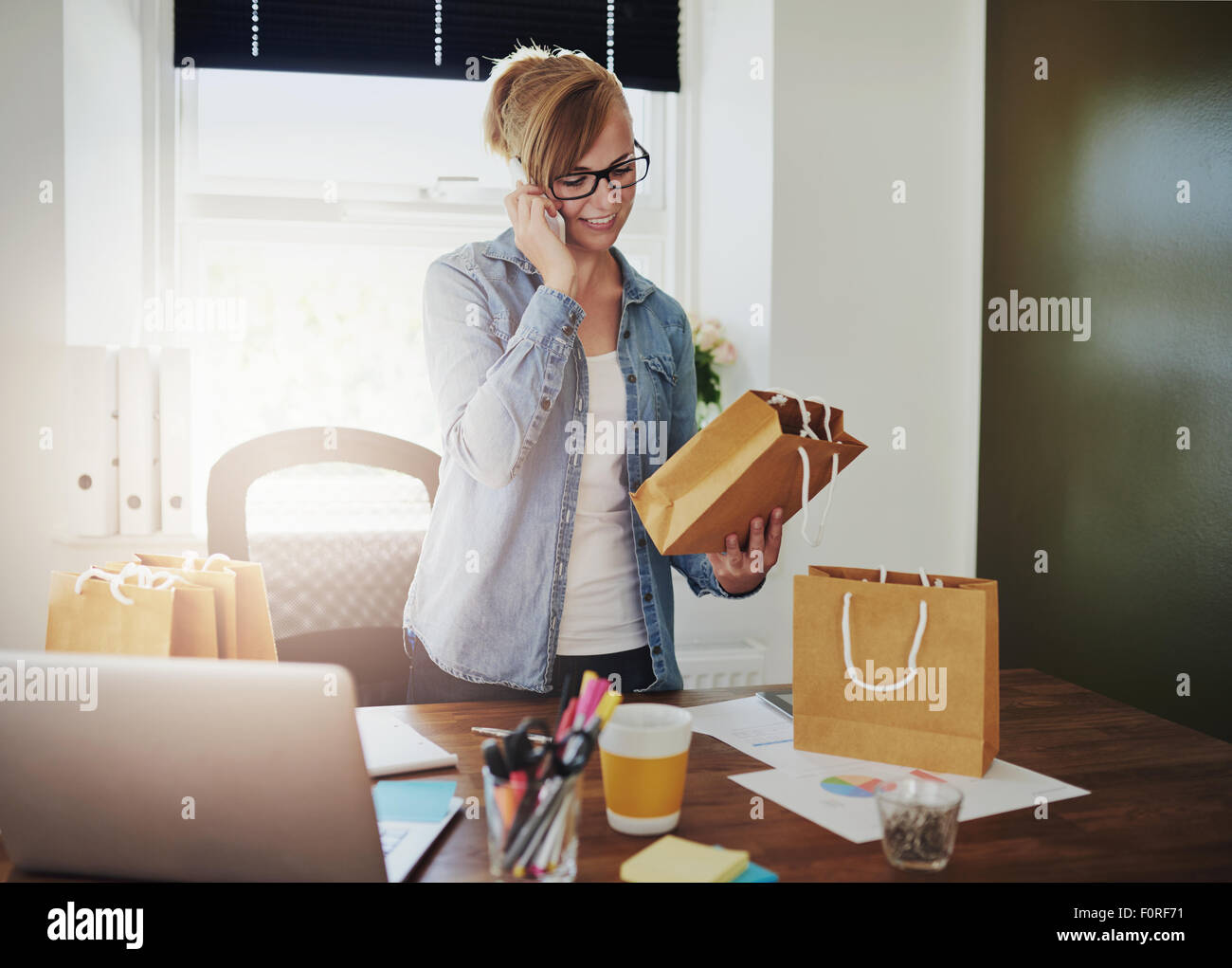 Motivated businesswoman placing orders on the phone for the packaging for her new online web based store as she - Stock Image