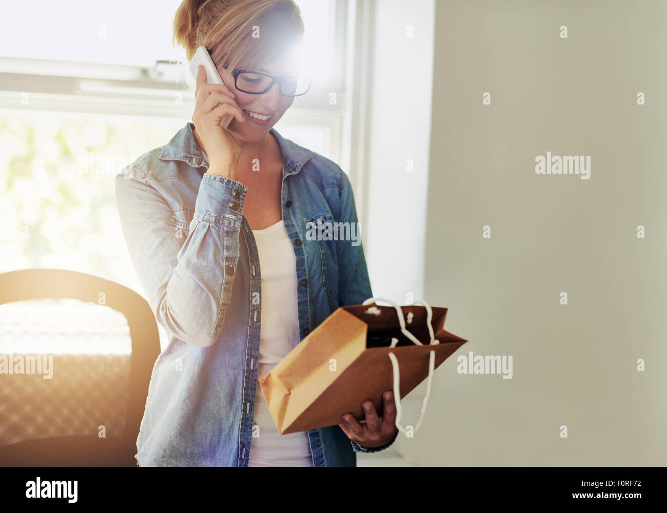Young businesswoman chatting on the telephone as she discusses packaging for the products for sale in her new e - Stock Image
