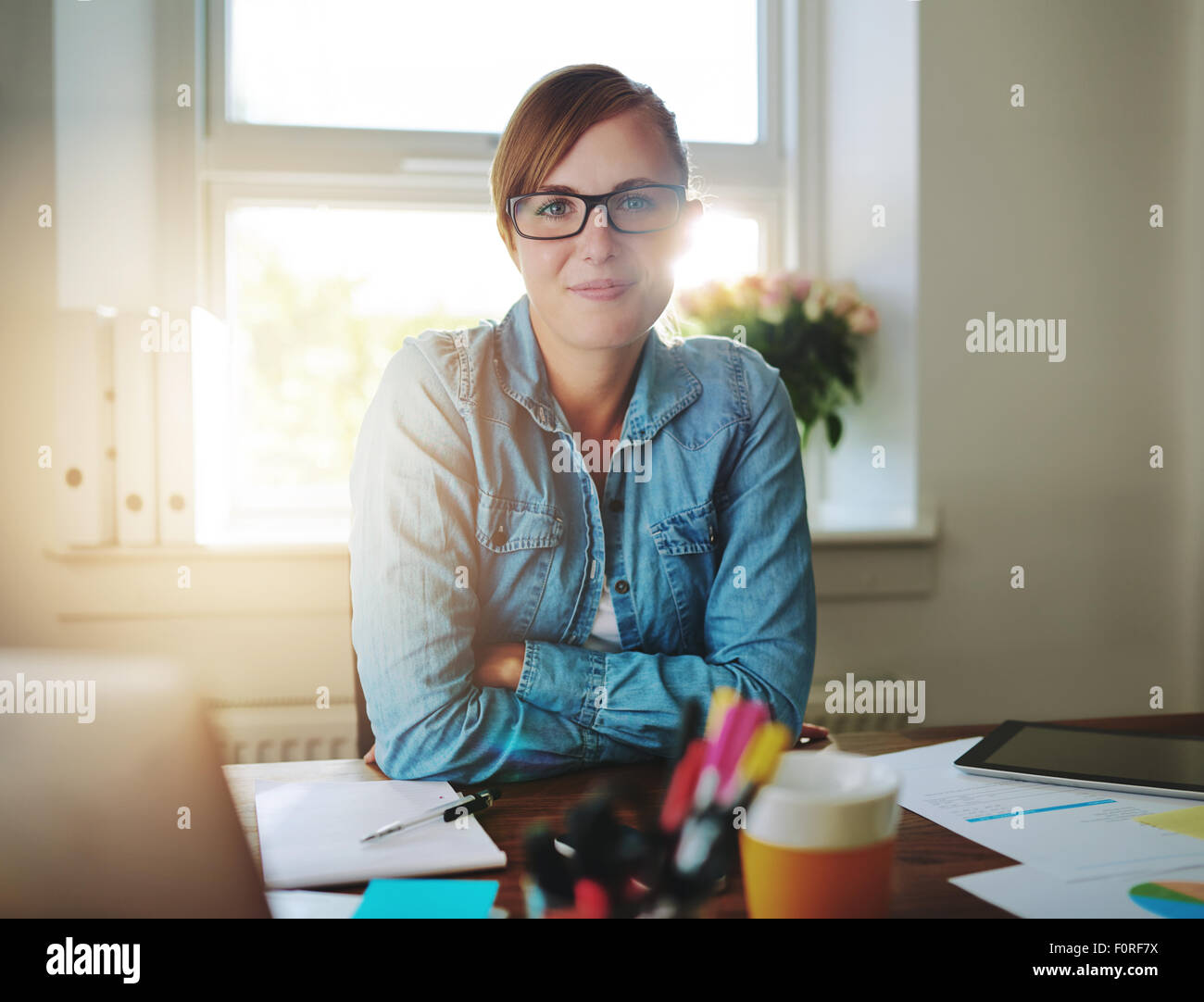 Successful business woman working at the office looking at camera - Stock Image