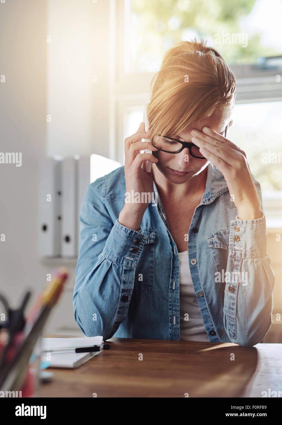 Concerned female entrepreneur talking on a phone as she sits at her desk in her home office with her head resting - Stock Image