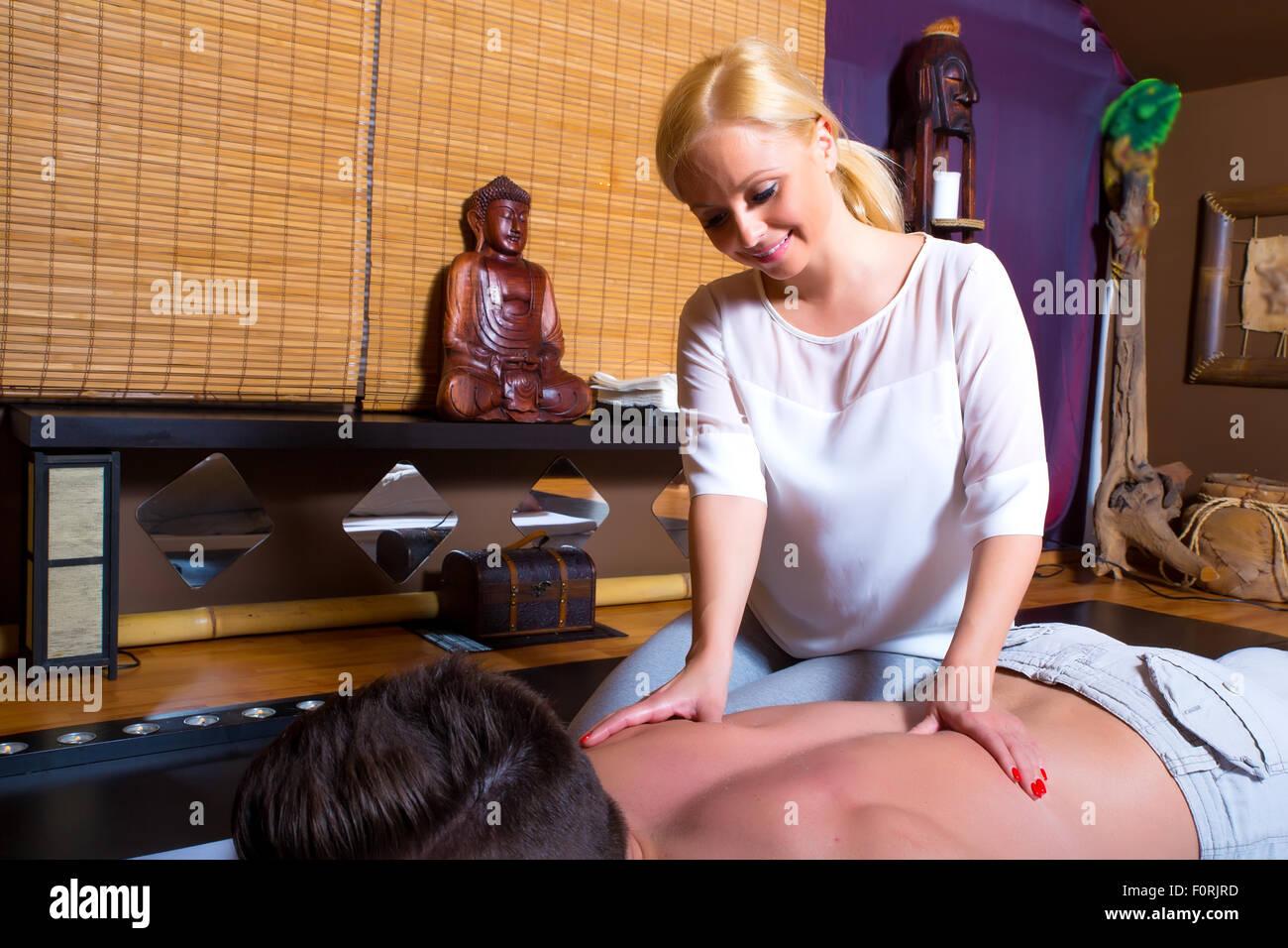 A young beautiful masseuse applying a massage. Stock Photo