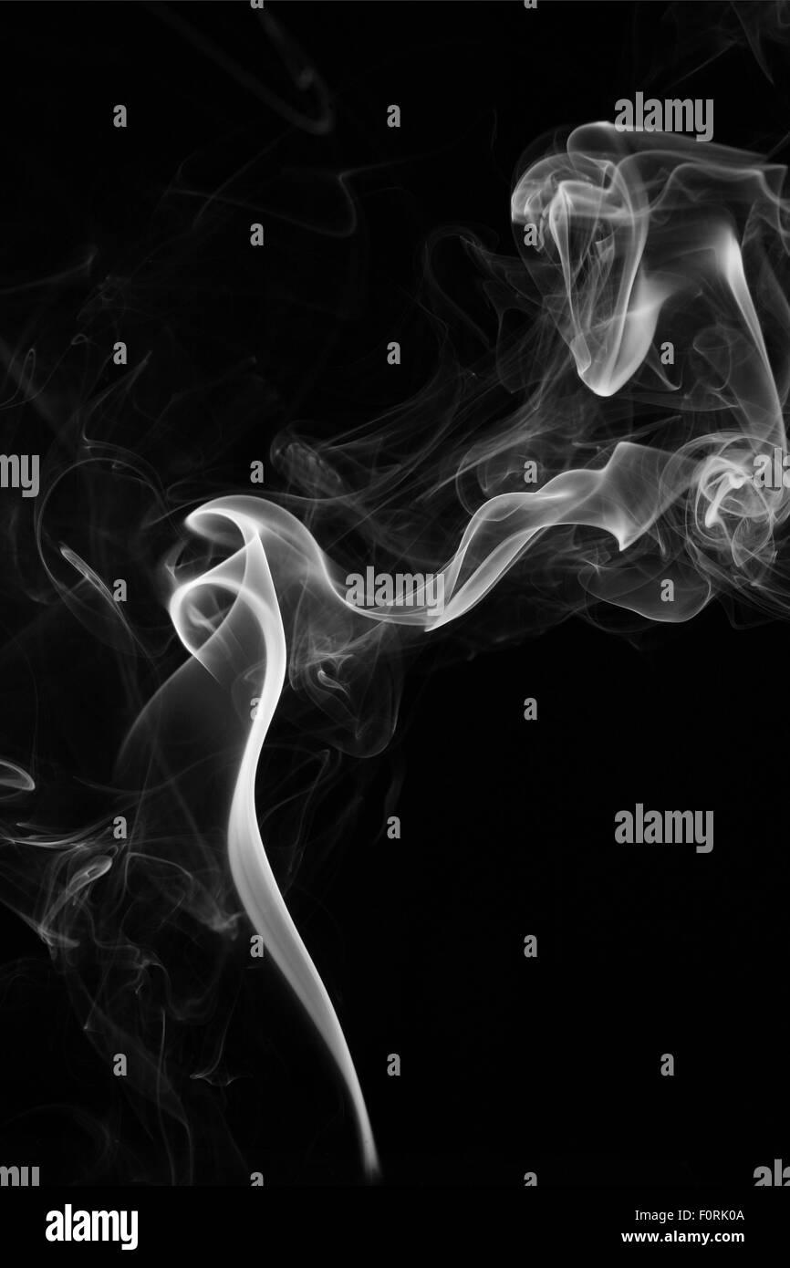smoke rising on a black background - Stock Image