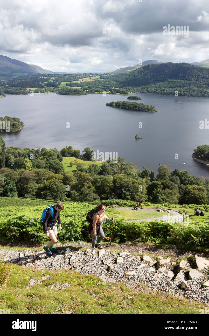 Walkers on the Lower Slopes of Catbells with Derwent Water Below, Lake District, Cumbria UK - Stock Image