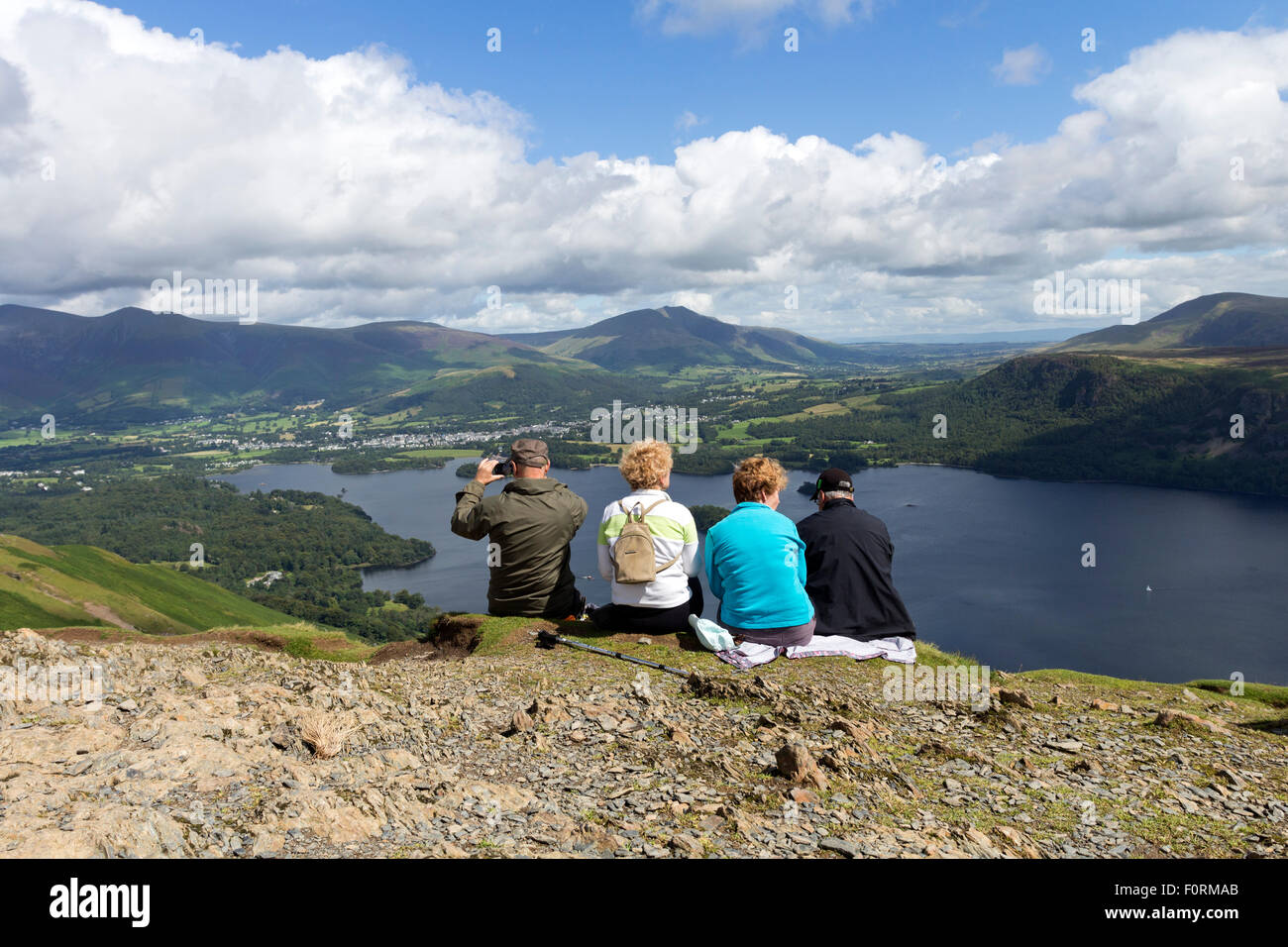 Four People Enjoying the View Across Derwent Water from the Summit of Catbells, Lake District Cumbria UK - Stock Image