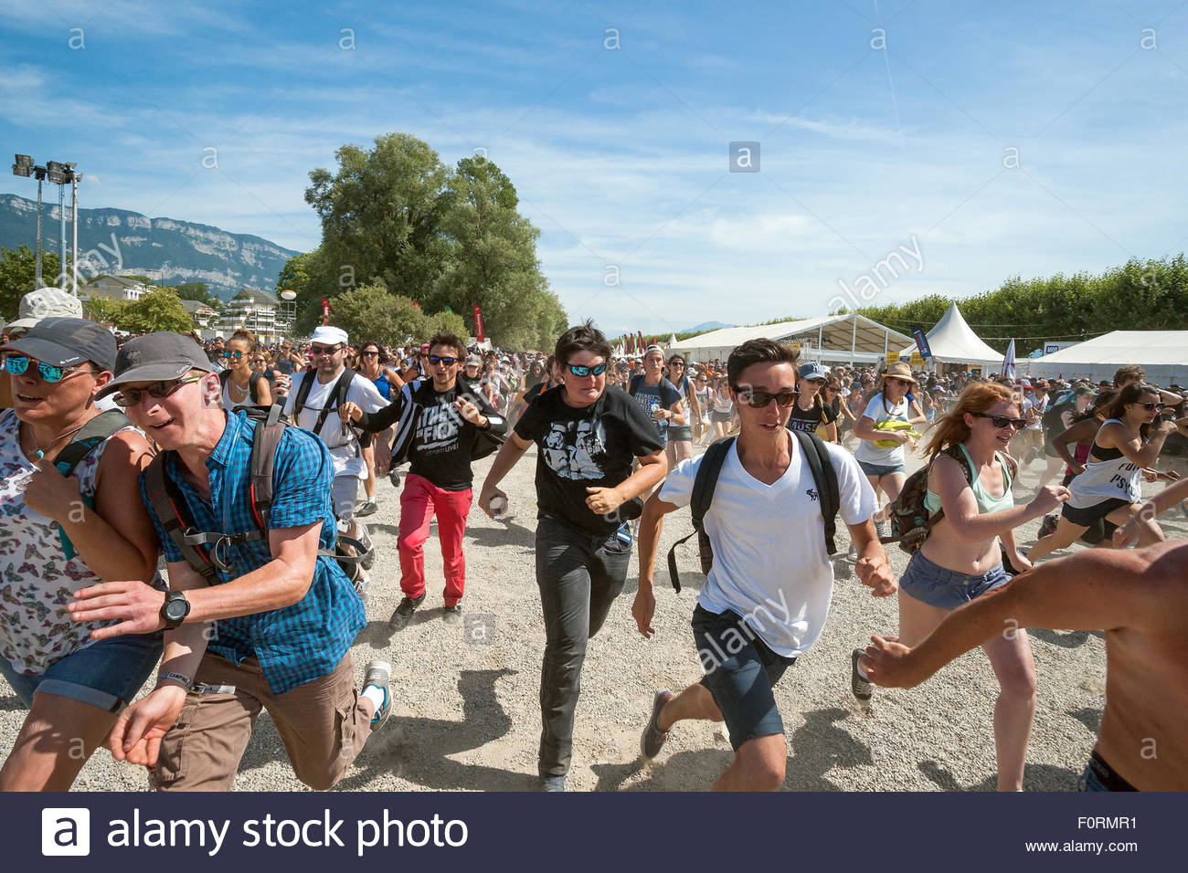 Young people running to see their favorite band at Musilac pop rock music Festival - Stock Image