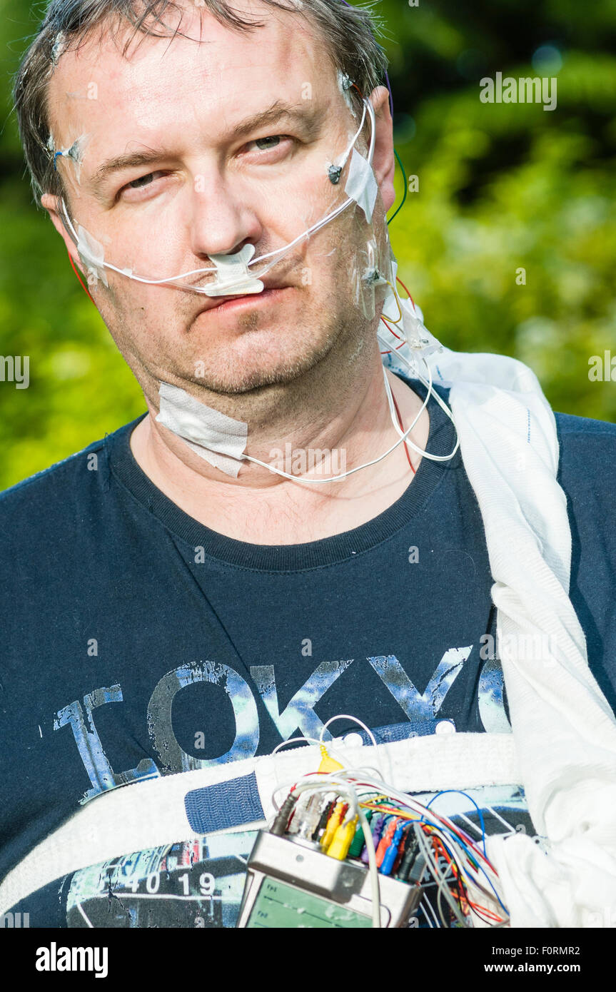 A middle aged man wears polysomnography equipment to measure brain activity, breathing and movement during sleep. - Stock Image