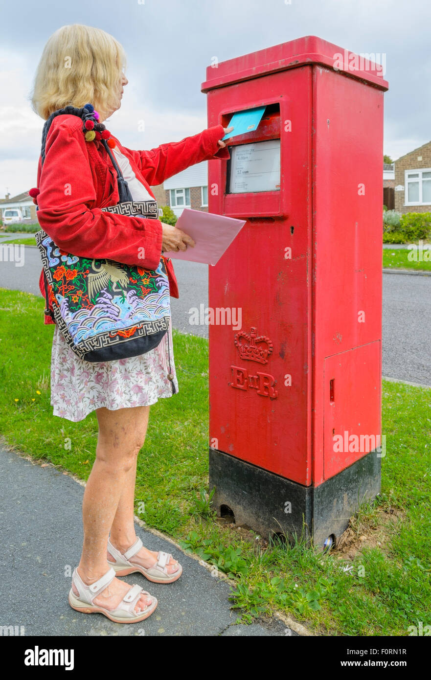 Senior woman mailing a letter in a red rectangular letter box in England, UK, Posting letters. Posting a letter. - Stock Image