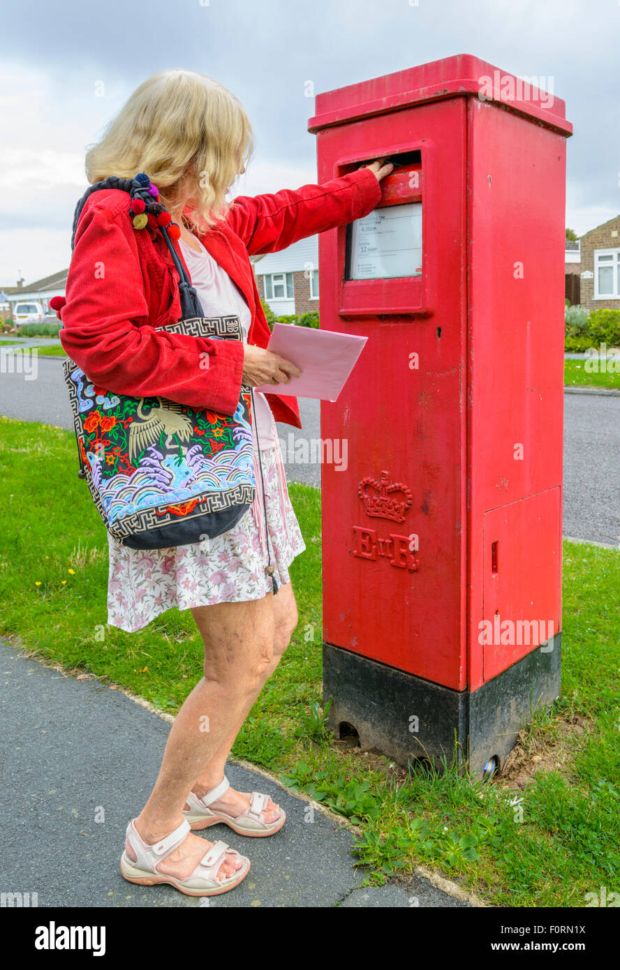 Middle aged woman posting a letter in a red rectangular letter box in England, UK. - Stock Image