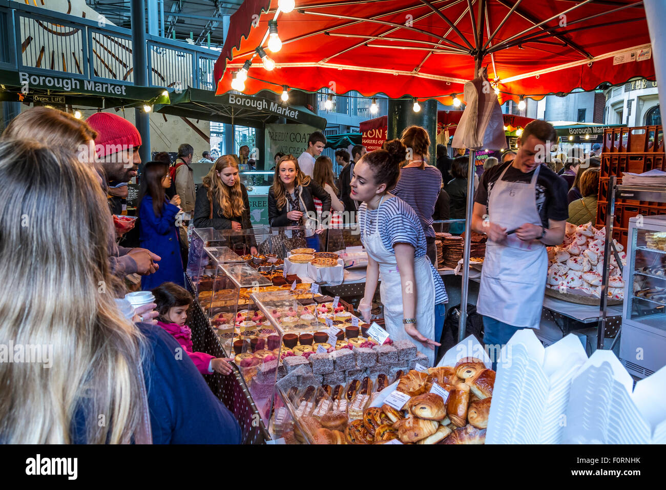 A Stall Holder serving crowds at a cake and biscuit Stall At Borough Market ,Bermondsey , London - Stock Image