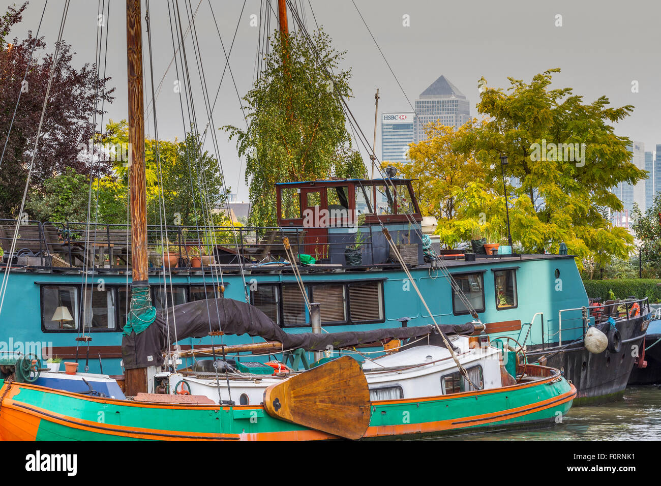 Houseboat and Yacht moored in front of trees on The River Thames near Bermondsey with Canary Wharf Towers including - Stock Image