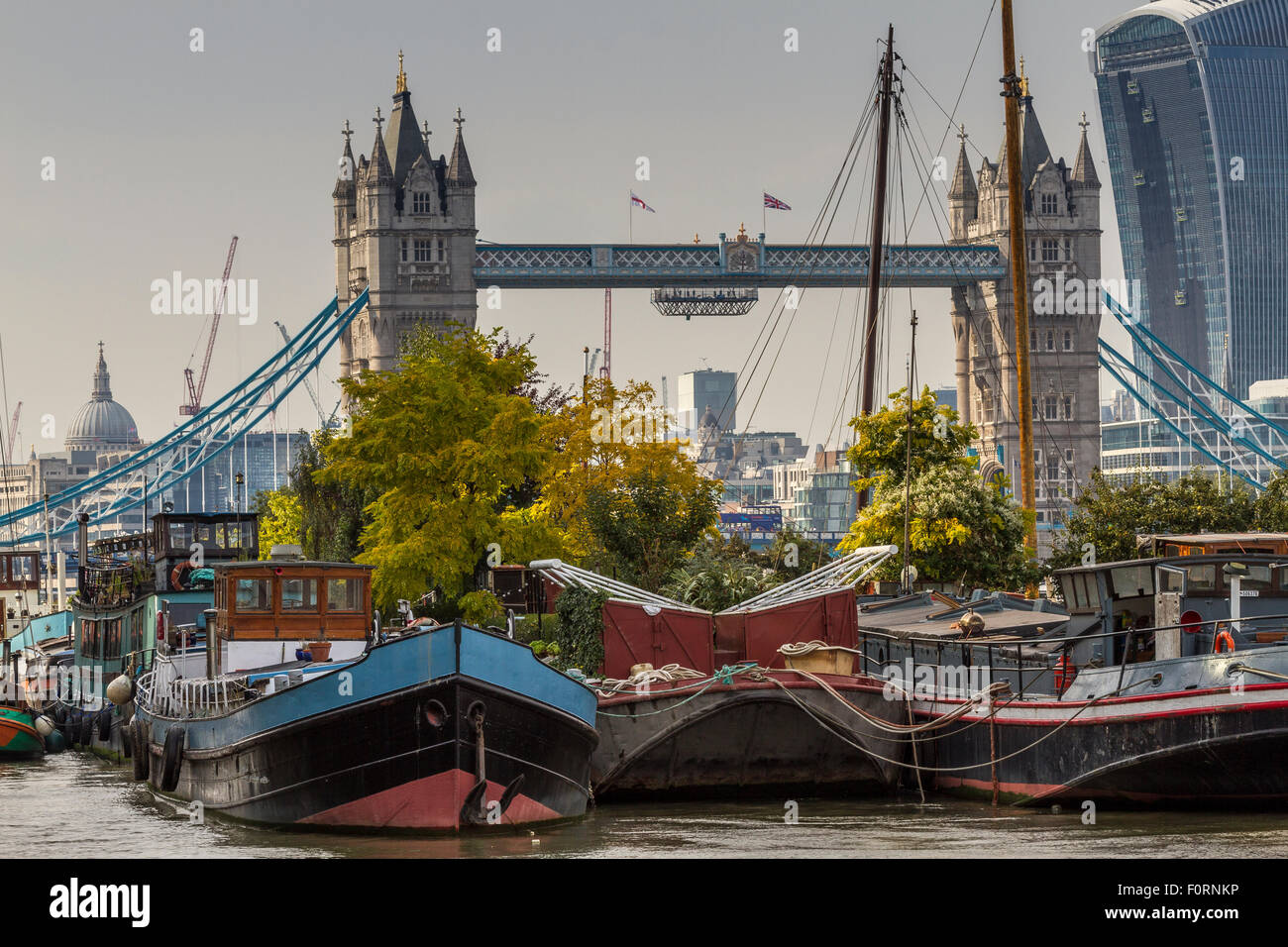 Houseboats and barges moored near Tower Bridge in Bermondsey  with 20 Fenchurch St , The Walkie Talkie Building, - Stock Image
