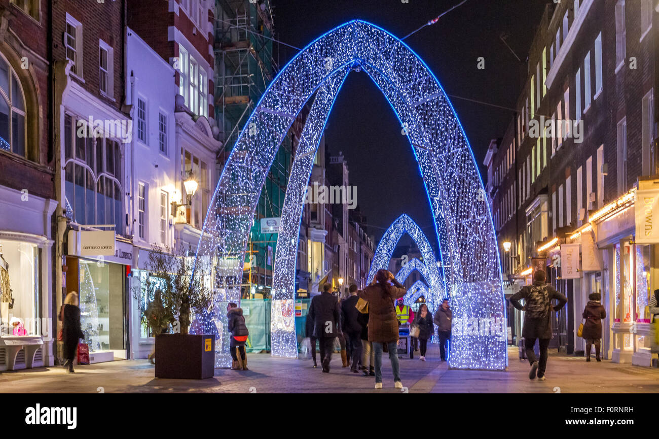 Christmas Lights and Christmas shoppers throng on On South Molton Street , London , with a blue Christmas Arch adorning - Stock Image