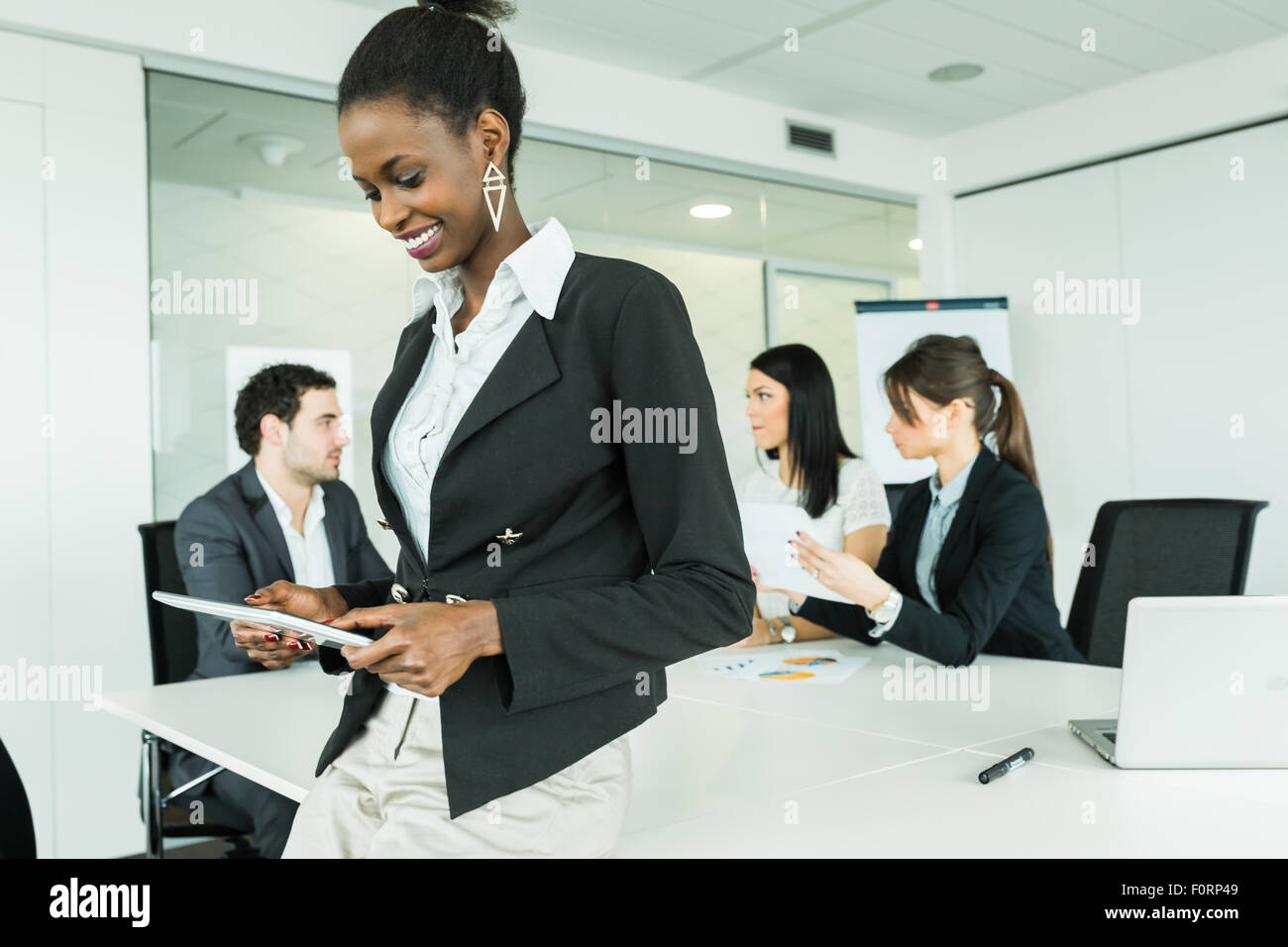 Beautiful, young, black, african businesswoman using a tablet at an office meeting - Stock Image