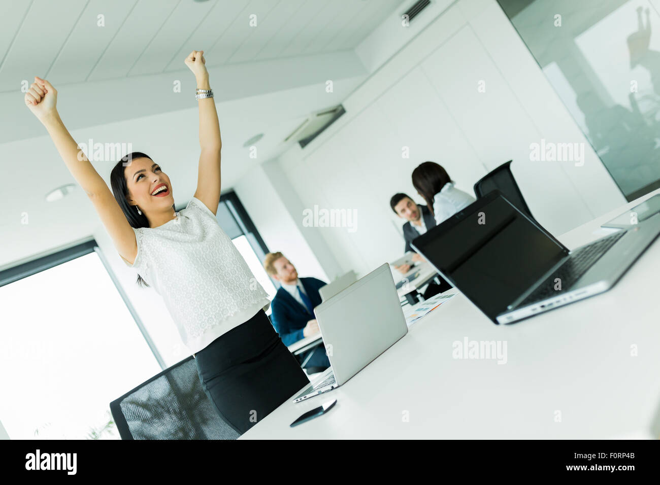 Businesswoman jumping from joy and raises both hands as a sign of success - Stock Image
