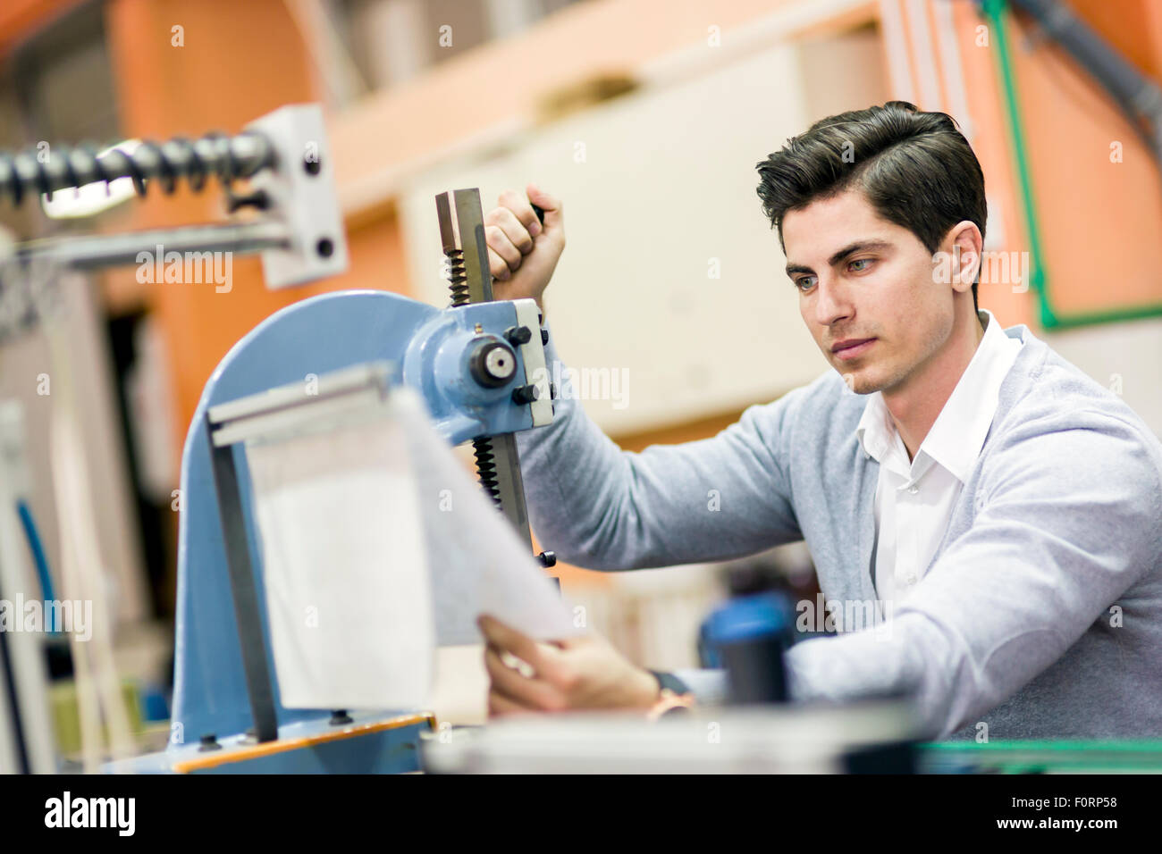 Young student working on a science project on a machine - Stock Image