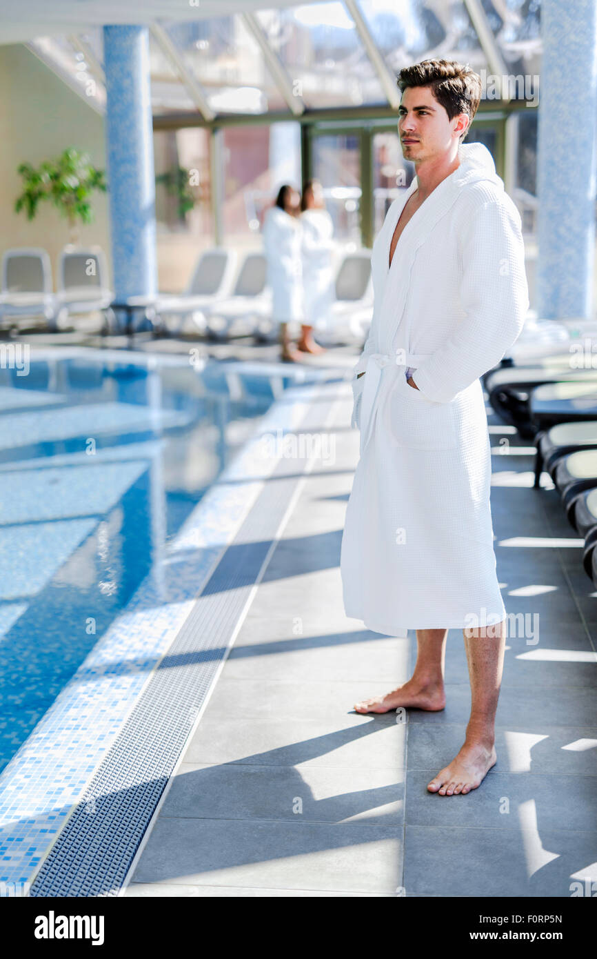 Man standing next to a  pool in a  robe and relaxing - Stock Image