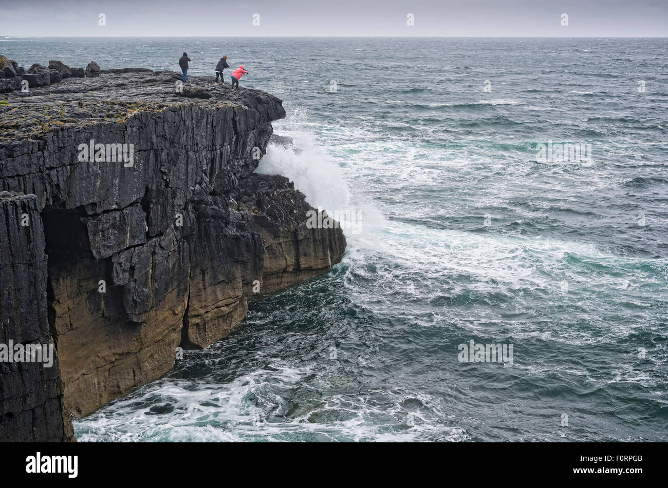 People taking photos of waves hitting cliffs at The burren, Co. Clare, Ireland - Stock Image