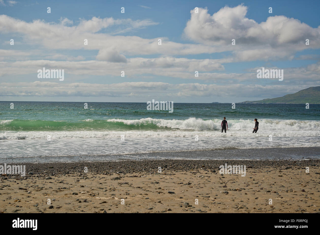 Surf instructors standing in the sea in wet suits - Stock Image