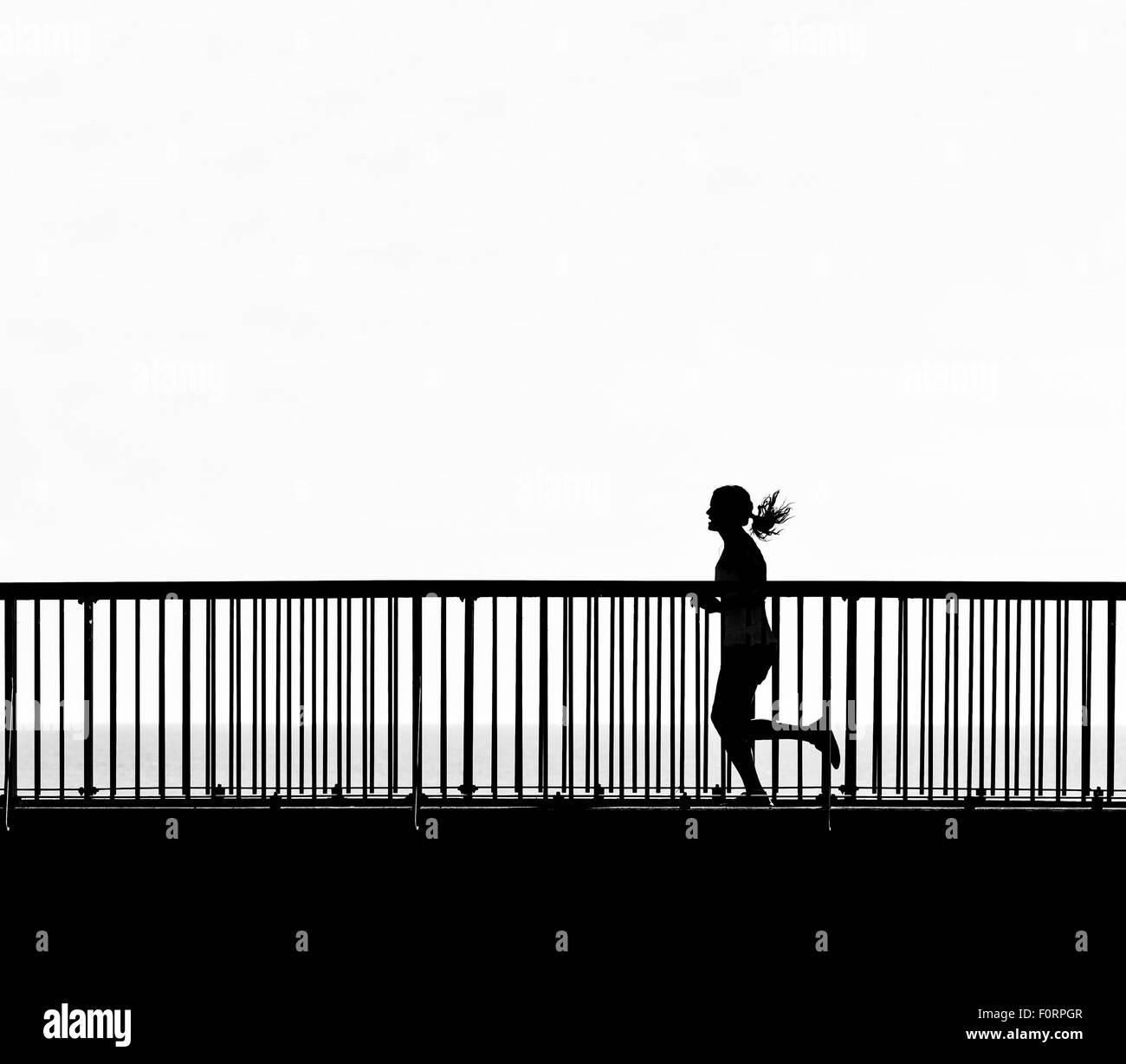 The silhouette of a woman jogging across the Louisa Gap Bridge in Broadstairs, Kent. - Stock Image