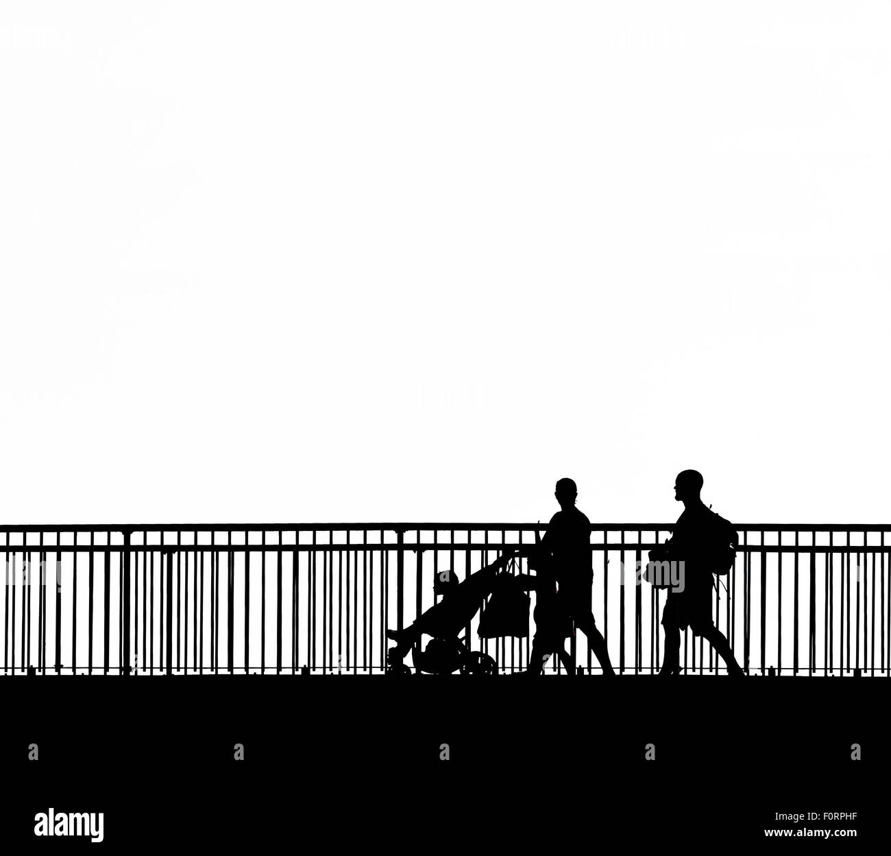 The silhouette of people walking across the Louisa Gap Bridge in Broadstairs, Kent. - Stock Image