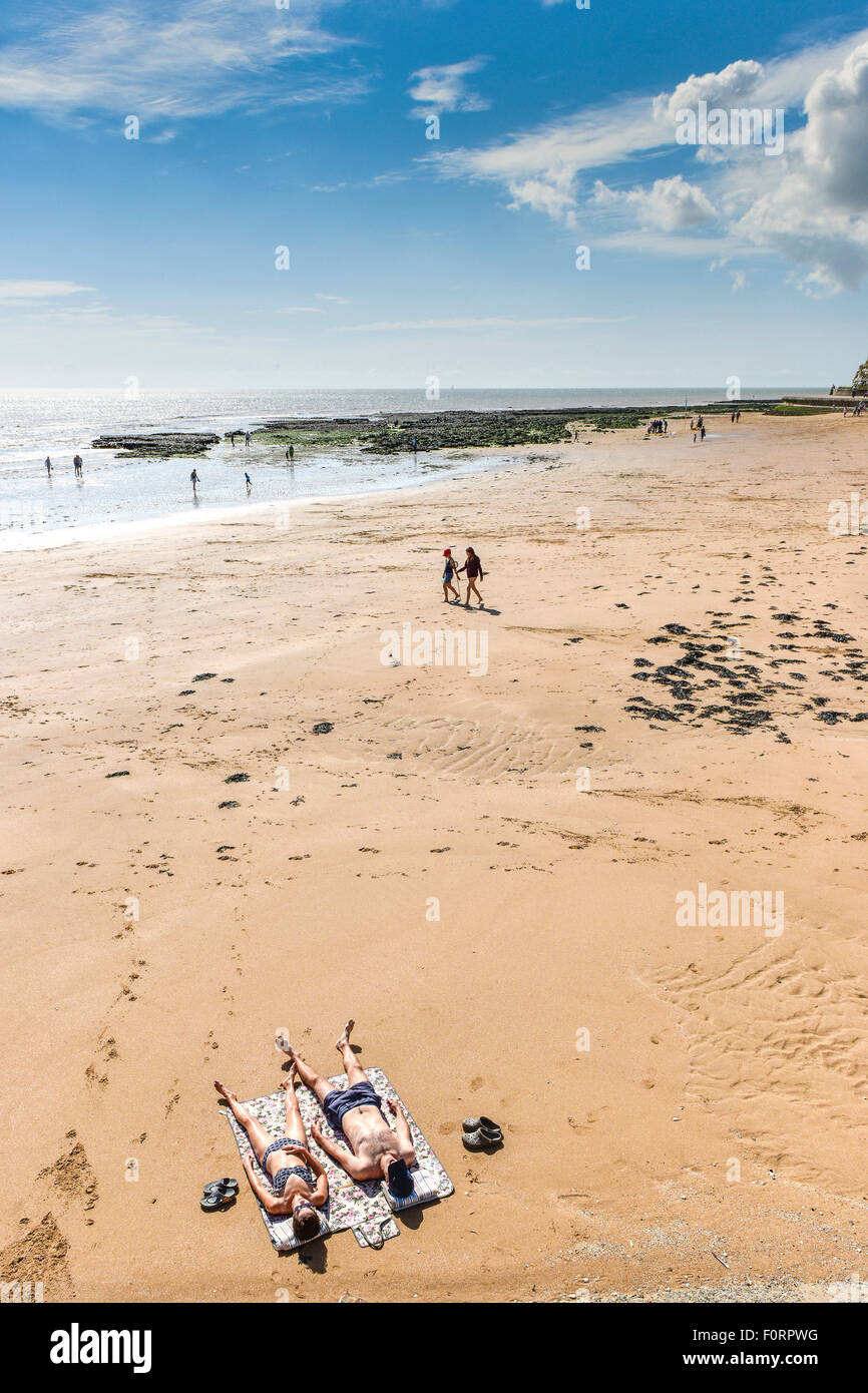 Sunbathers on a beach at Broadstairs in Kent. - Stock Image