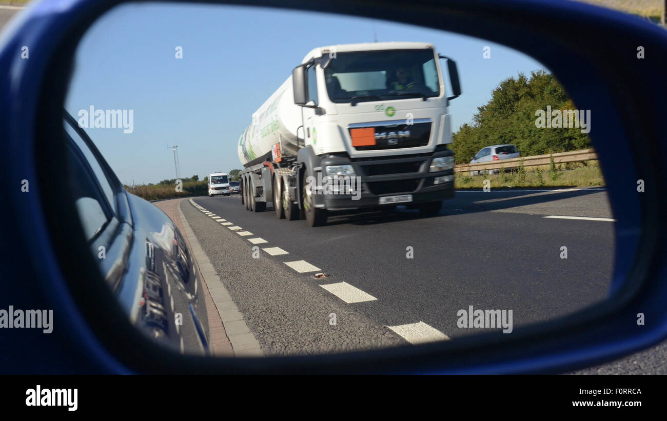 lorry traveling on the a1/m motorway reflected in vehicle wing mirror leeds uk Stock Photo