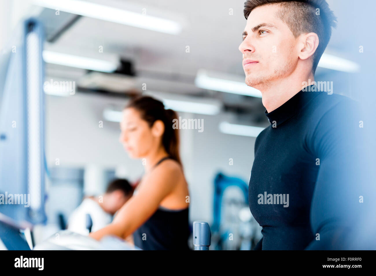 Group of healthy young people using treadmill and elliptical trainer in a gym Stock Photo