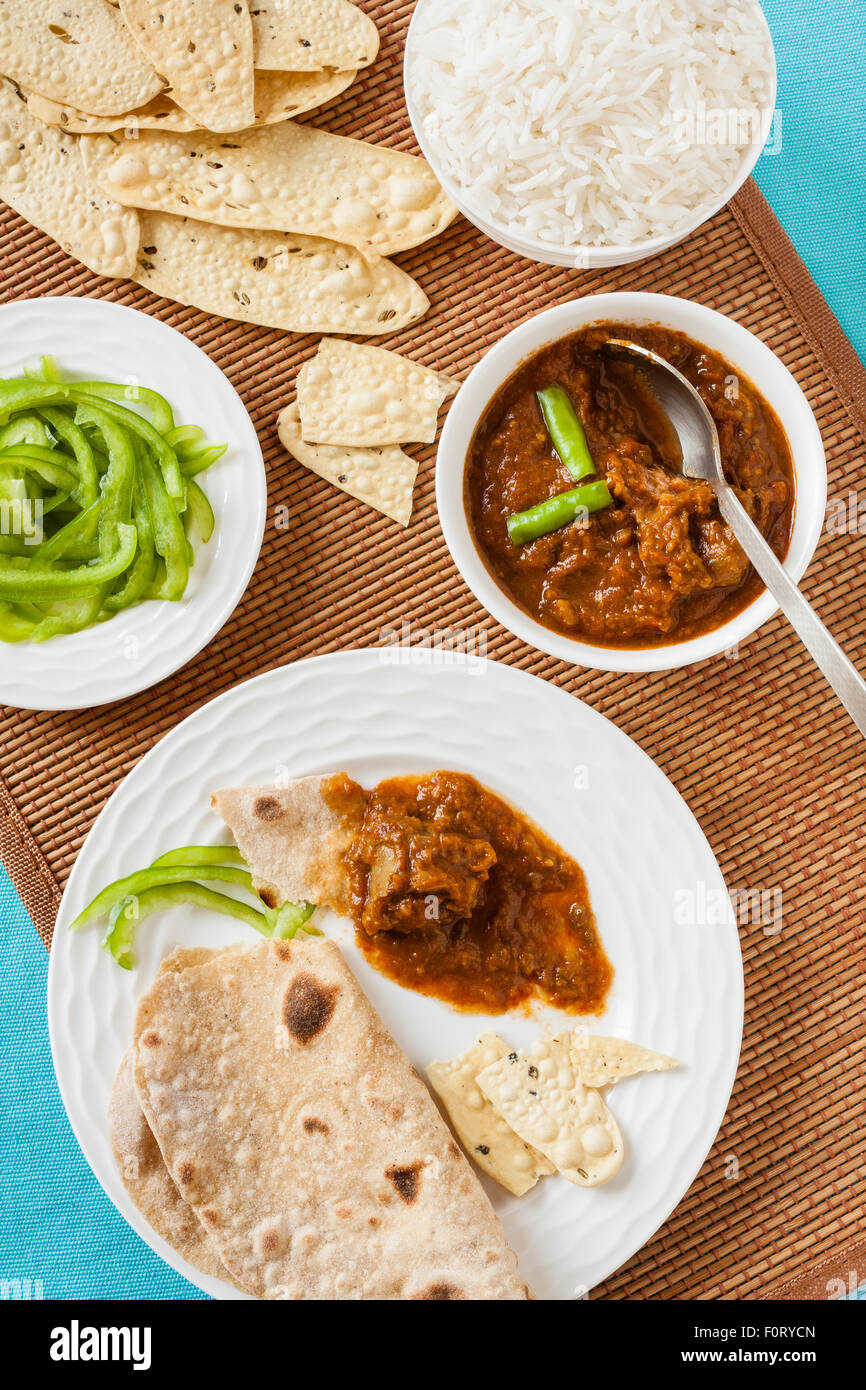 Tasting Indian mutton rogan josh meal with rice and chapati. This spicy hot Kashmiri dish uses red chilli (cayenne - Stock Image