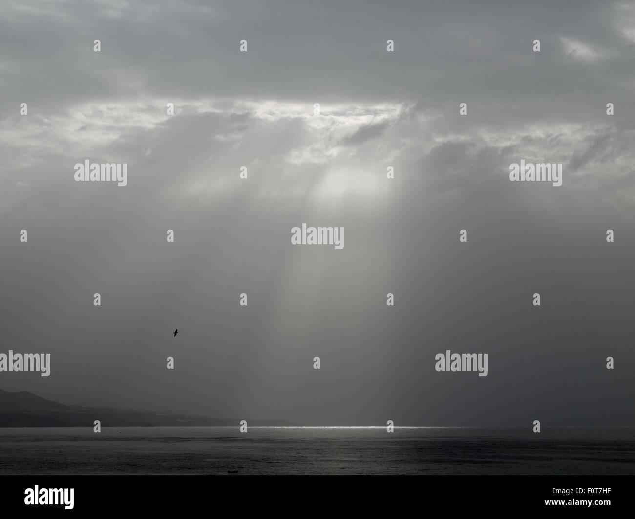 cloudy sky with a single gap in the clouds through which sun rays come - Stock Image