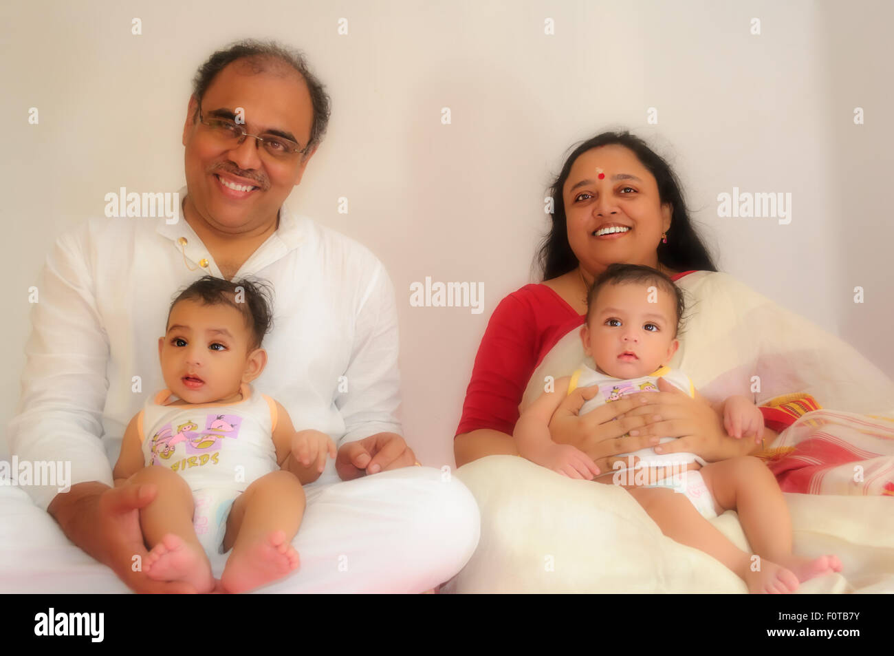 Portrait of a happy family of parents with twin baby boys showing bond love affection and togetherness with copy space