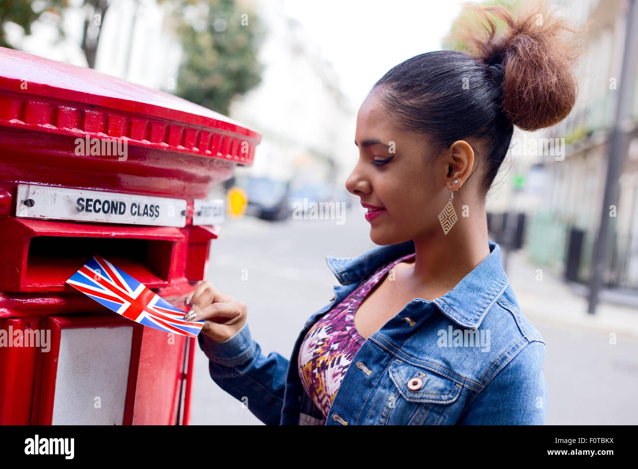 young woman posting a postcard in London Stock Photo